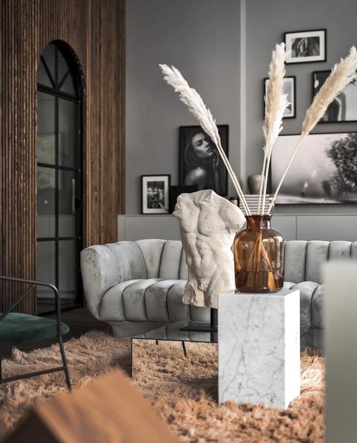 dame jeanne pampa canapé velours gris clair statuette objets déco style moderne peinture murale tendance grise cadre photo blanc et noir