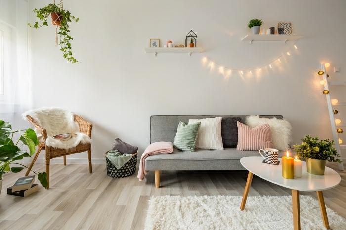 déco salon cocooning style scandinave canapé vintage gris coussins dépareillés table basse bois scandinave déco avec plantes vertes et guirlandes lumineuses