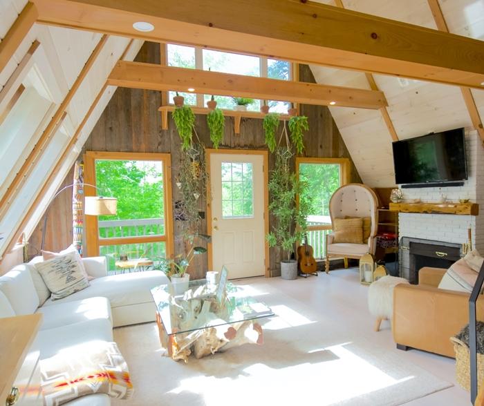 deco boho chic mur briques blanches poutres apparentes plafond canapé d angle coussin motifs ethniques table basse verre et bois brut chaleureux et cocooning
