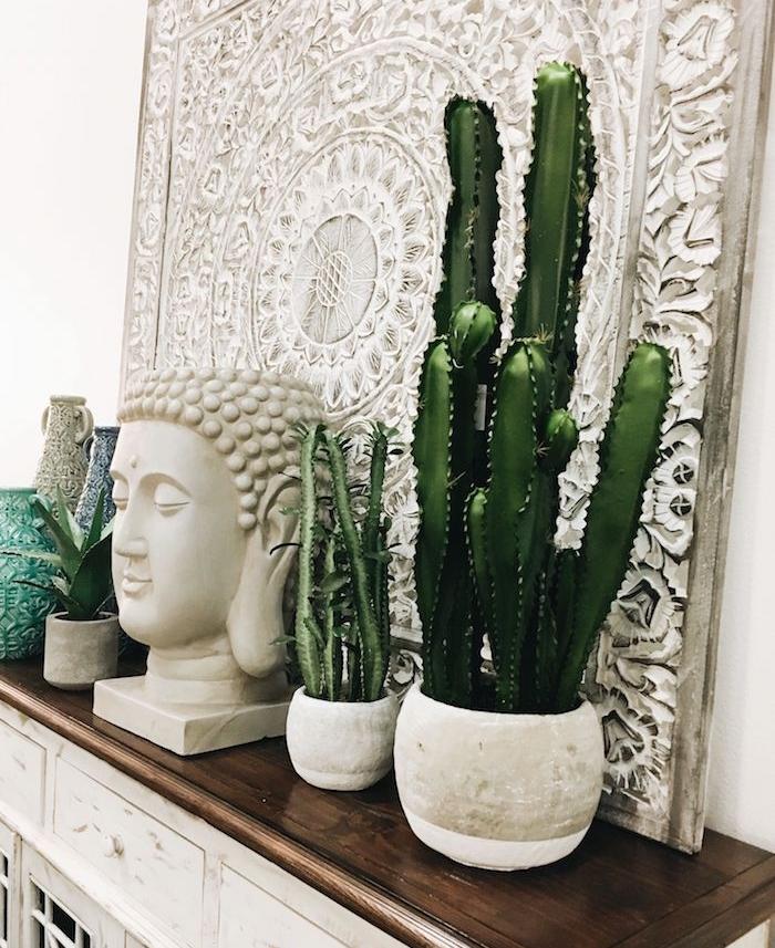 deco depaysante avec des pots de cactus de tailles variées statuette de bouddha rangés sur meuble bois et blanc vieilli