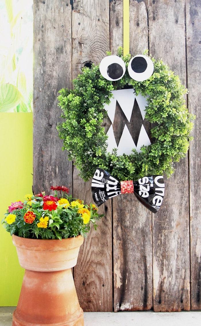 deco halloween exterieur a faire soi meme couronne de branches avec des yeux et des dents de papier et noeud de papillon sur porte de bois plante en pot