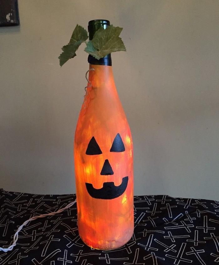 deco halloween facile a faire bouteille de verre décorée de peinture orange avec motifs jakc o lantern en peinture noire