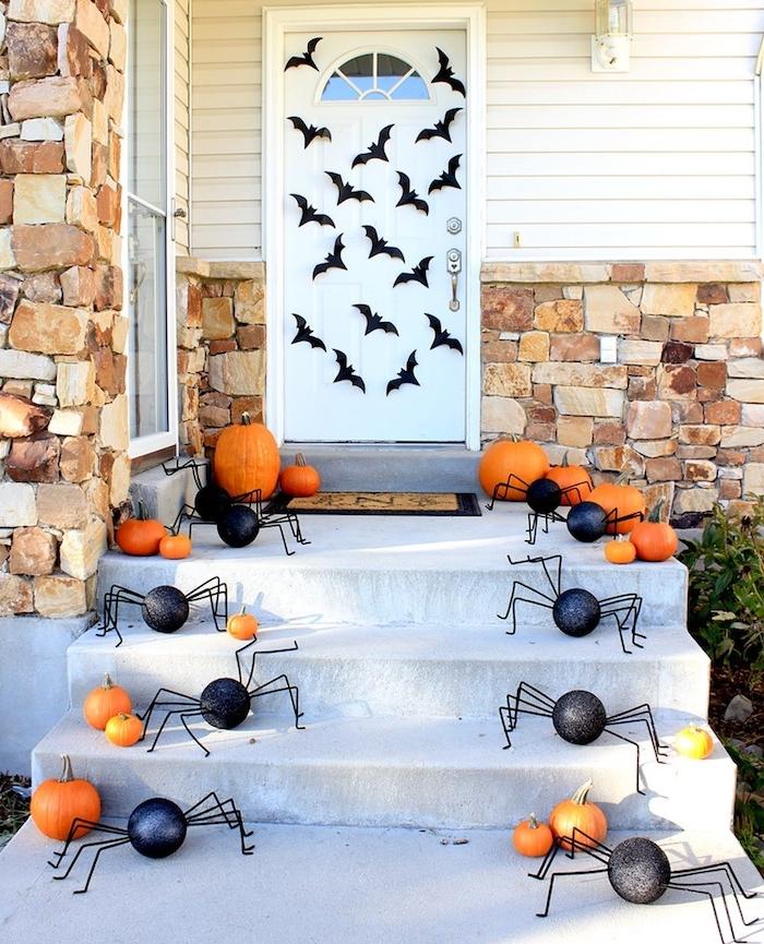 deco porte halloween araignées en papier de couleur noire des araignées et multitude de citrouilles et potimarrons de halloween
