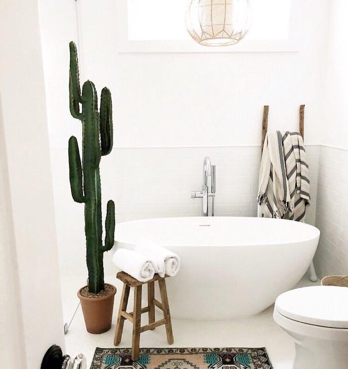 deco salle de bain avec baignoire blanche tabouret bois brut tapis oriental carrelage blanc granc dactus en pot