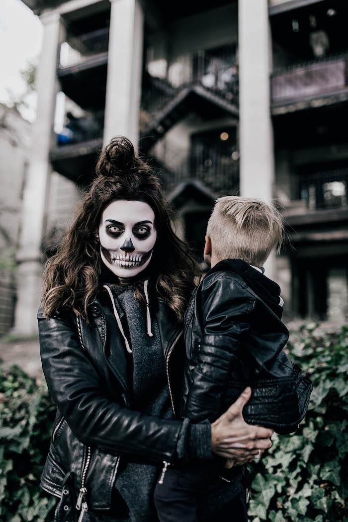 deguisement couple drole maquillage effrayant des vetements noirs maquillage squelette mere et fils devant un batiment