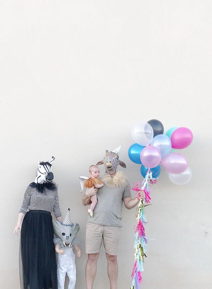 deguisement ridicule comme des animaux de fete une famille masque avec bequcoup de ballons devent mur blanche