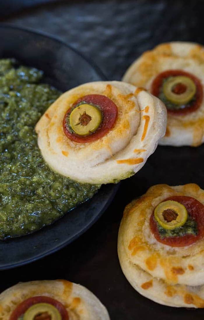 des balles oculaires sur des petits pizzas garni de sauce pesto toast halloween