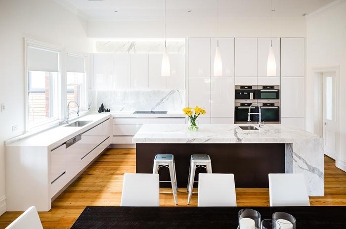 design cuisine ouverte vers salle à manger table repas bois foncé chaise blanche cuisine en marbre lampe suspendue blanche