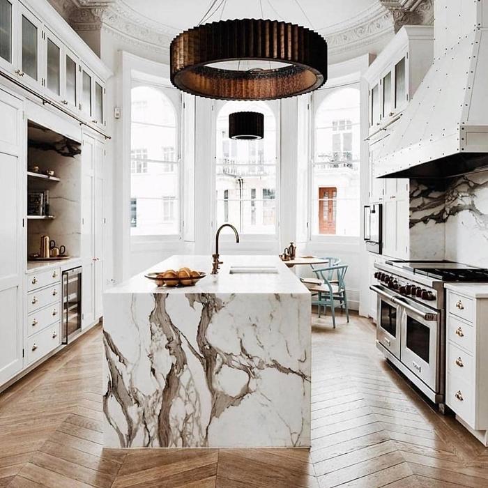 design intérieur agencement cuisine en parallèle avec îlot central cuisine blanche et marbre parquet bois accents métal rose gold