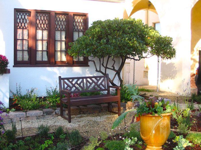 devanture maison style mediteraneen banc et dentetre en chene dans une maison blanche ensoleillée