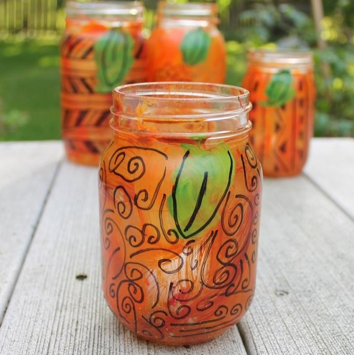 diy halloween photophore dans pot en verre décoré de peinture couleur orange volutes au stylo feutre et feuille deco halloween a faire soi meme