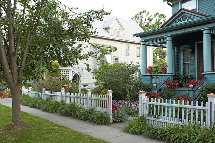 entree exterieur maison palissade en bois blanche devant un beau jardin de cour devant