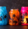exemple de photophore halloween a faire soi meme dans pot en verre décoré de papier de soie et des silhouettes noirs de papier deco halloween a faire soi meme