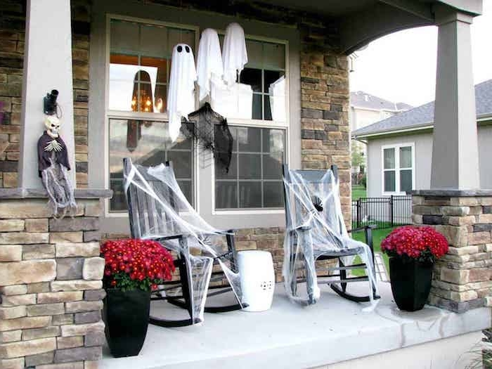 exemple terrasse avec deco halloween0diy exterieure chaises à bascule décorées de toiles d araingée pots avec fleurs d automne fantomes en balllon et toile blanche