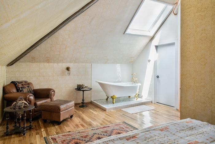 fauteuil cuir marron tapis motifs ethniques chambre avec salle de bain ouverte baignoire autoportante pieds dorés