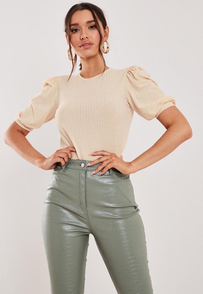 femme en pantalon cuir et blouse manches bouffantes en beige avec des boucles d oreilles