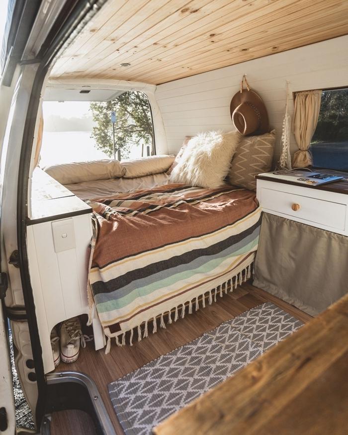 fourgon aménagé interieur cocooning déco lit coussin fausse fourrure blanche revêtement plafond bois murs blancs
