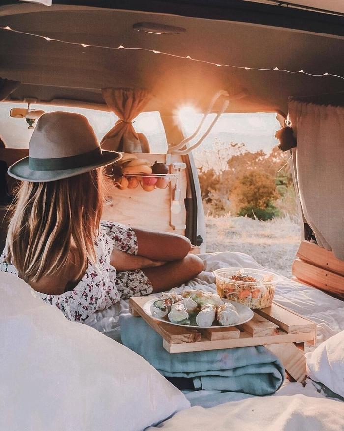 fourgon aménagé interieur vie bohème voyage nomade fille véhicule lit guirlande lumineuse déco lit cocooning coussins