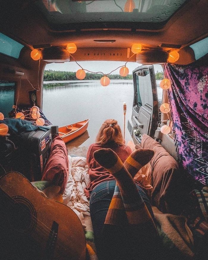 guirlande lumineuse fenêtre guitare vue paysage véhicule aménagé avec lit coussins décoratifs plaid objets textile bohème déco