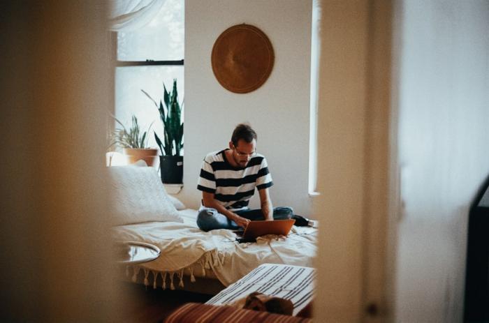homme assis sur son lit chambre bien aménagée style bohème chic originale idée