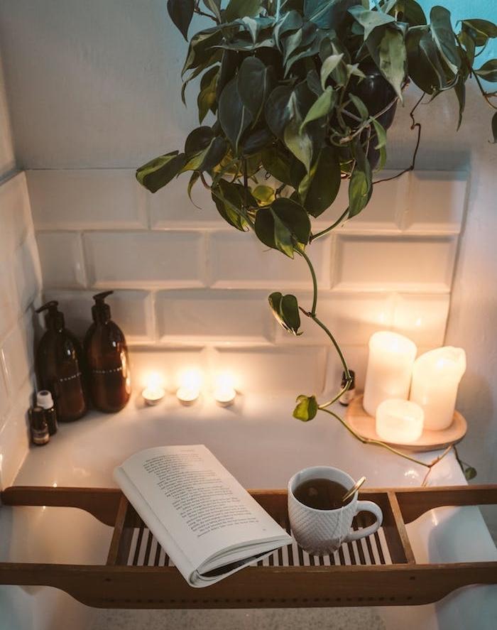 idée de plante salle de bain suspendue livre et tasse de café avec des bougies et huiles essentielles baignorie salle de abin cocooning blanche