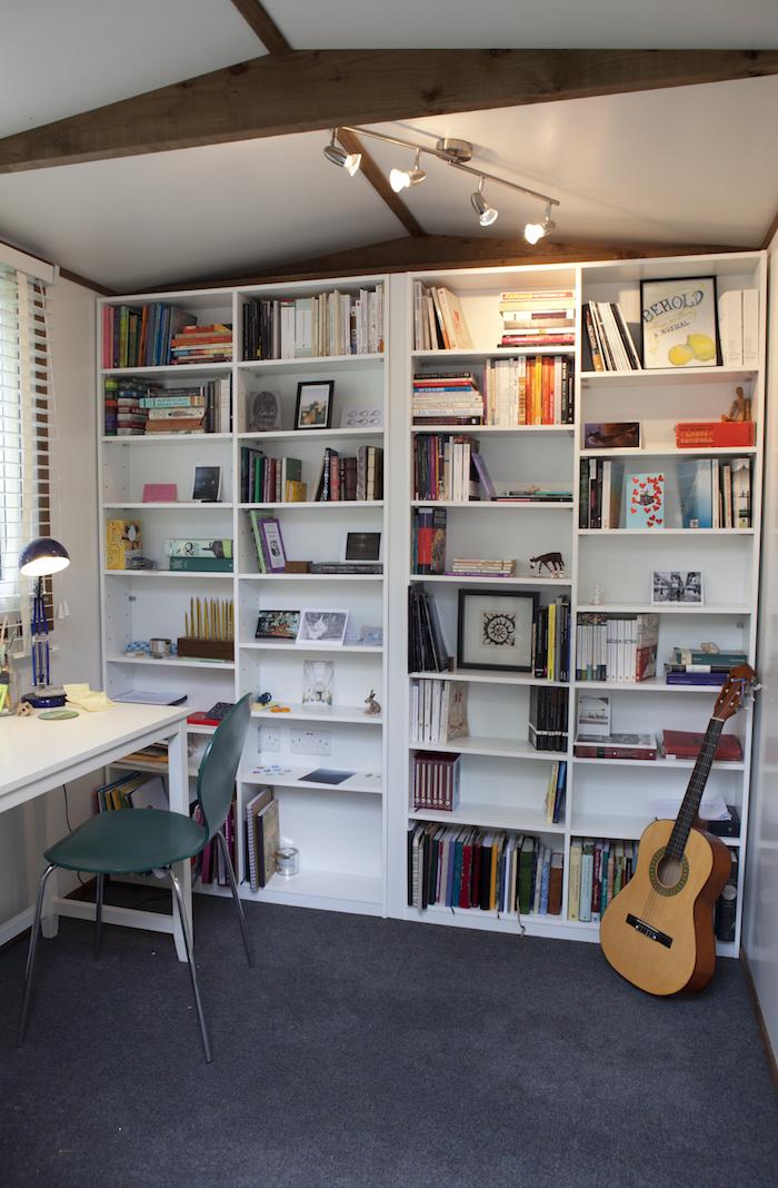 idee deco bureau avec une grande etagere et une guitare tapis au plancher et une chaise turquoise