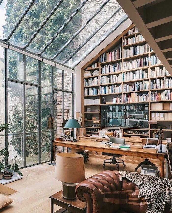 idee deco bureau grande biblioteaque collection de livres mur et plafond vitres avec beaucoup de veredure en dehors