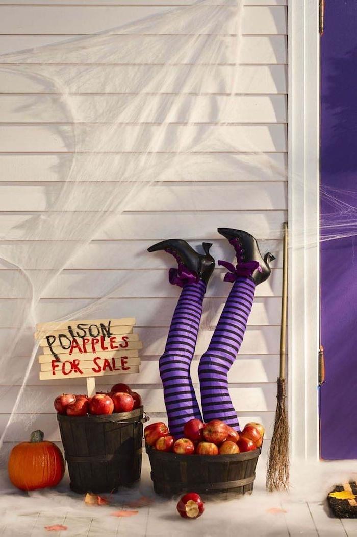 jambes de sorcière dans des sceaux de bois remplies de pommes toile d araignée artificielle