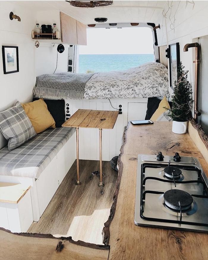 jeté lit frange noir et blanc table bois canapé coussin jaune comptoir bois brut cuisine gaz électricité van aménagé