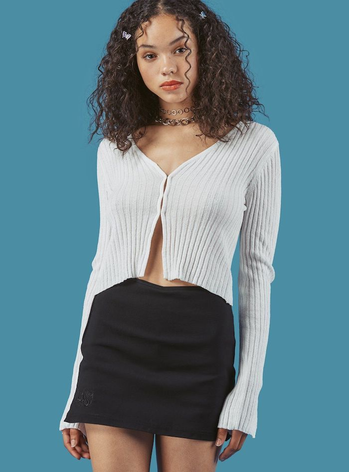 jeune femme look année 2000 chemise boutonnée et jupe corte noire avec un colier type choker