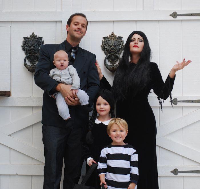 la famille addams idee costume halloween devant une porte blanche costumes noirs des longues tresses