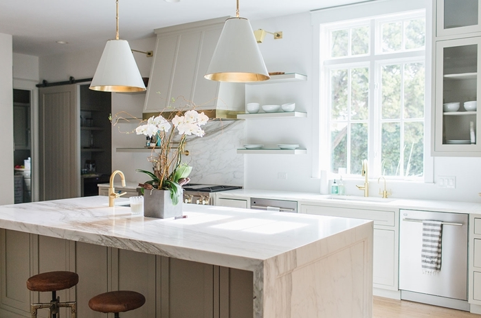 lampe suspendue blanc et or tabouret cuir noir vase béton plan de travail effet marbre fenêtre carreaux armoires verre bois blanc