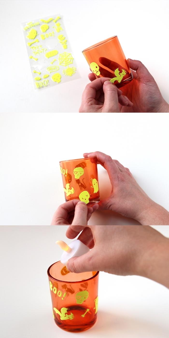 lanterne halloween a faire soi meme dans petit pot en verre teinte d orange avec déco de stickers et bougie led à l intérieur