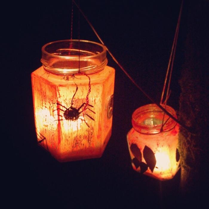 lanterne halloween dans pot en verre bougie halloween et motifs feuilles araignée et peinture orange pour decorer l exterieur du pot