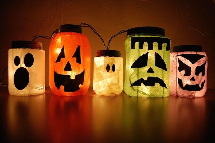 lanterne halloween décoré de petits bouts de papier de soie et des stickers noirs motif monstre jack o lantern et guirlande lumineuse