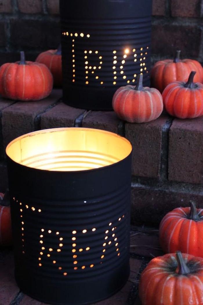 lanternes en boite de conserve recyclée et repeinte de noir avec des trous et mini citrouilles autour