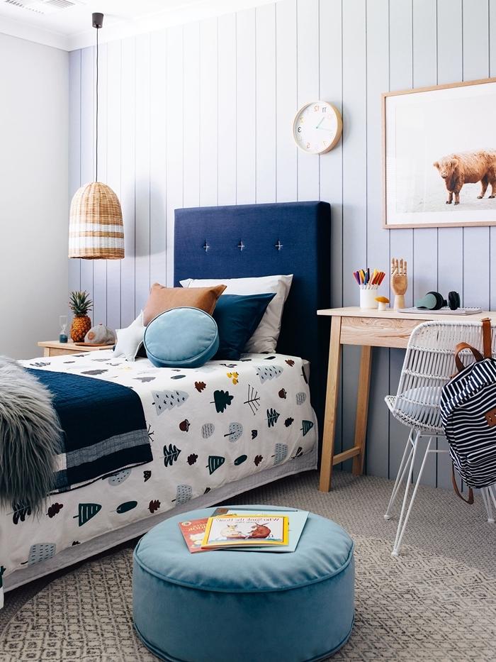 lit avec tete de lit dans une chambre enfant bureau bois clair revêtement mur panneaux bois horloge bois table de chevet bois ottoman bleu pastel