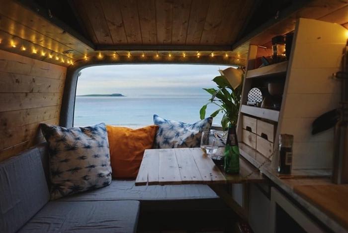 mini van aménagé camping car déco bohème meubles convertibles table repas canapé lit coussins décoratifs guirlande led