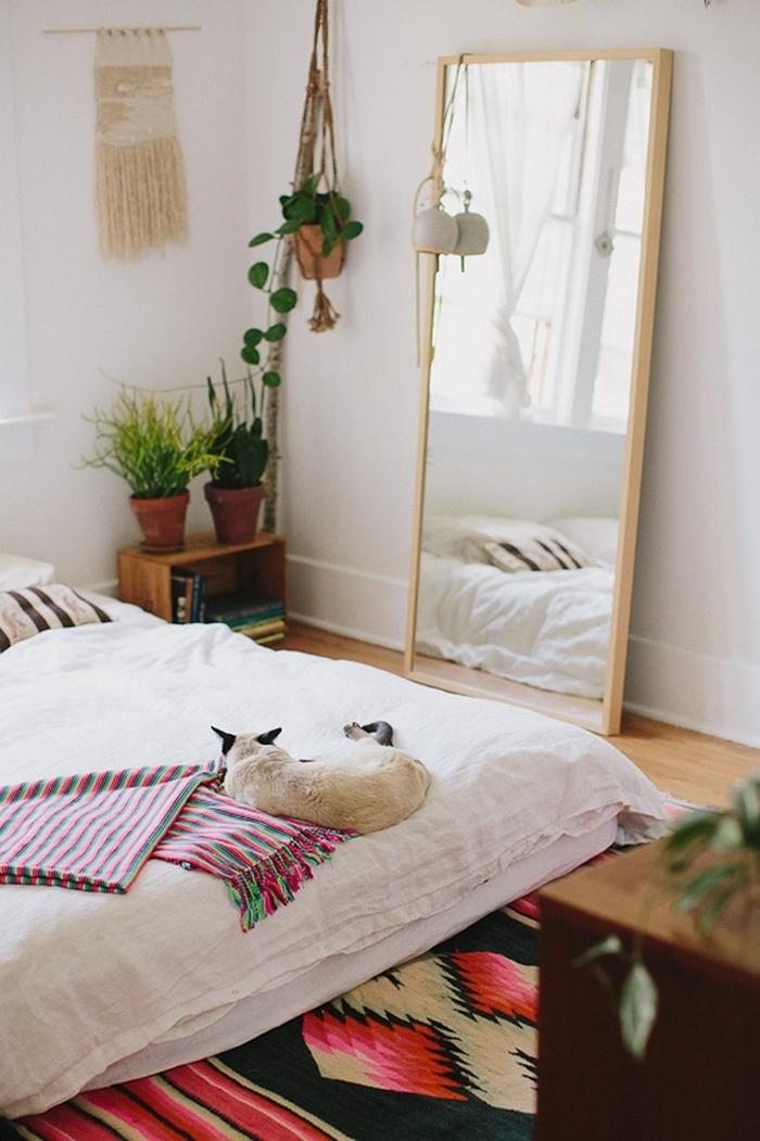 miroir cadre bois chambre style bohème tapis multicolore meuble bois rangement livres pot fleur terre cuite suspension macramé