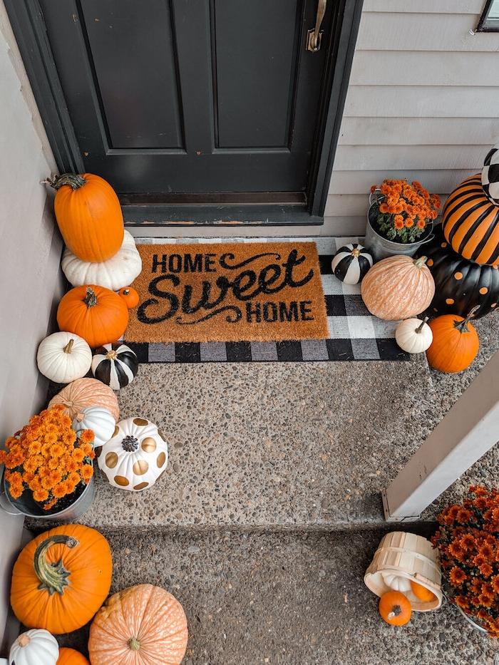 modele de décoration halloween à fabriquer en citrouilles naturelles et repeintes et décorés et fleurs orange en seaux de zinc