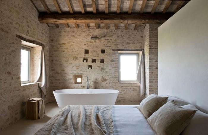 mur briques plafond avec poutres apparentes salle de bain dans chambre baignoire autoportante couverture de lit beige