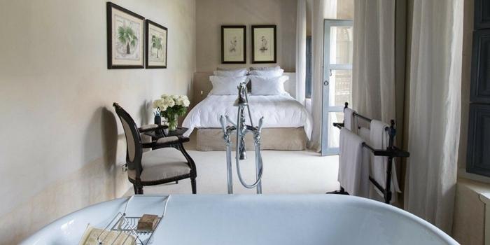 mur cadres photos noirs chaise noire baignoire autoportante déco de lit cocooning chambre avec salle de bain ouverte