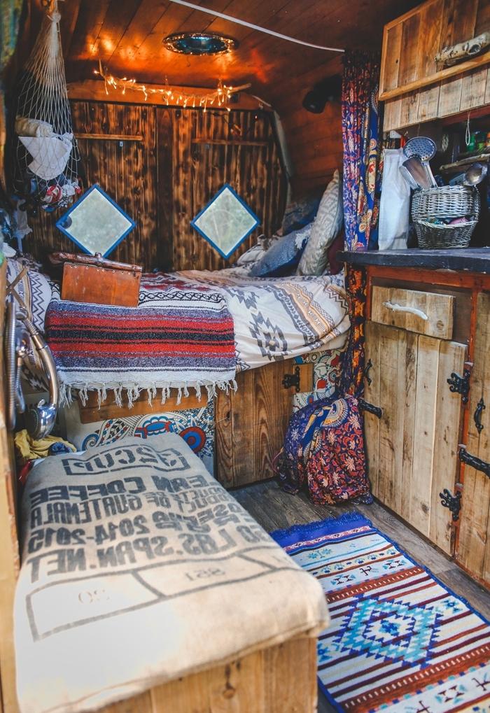 objets textiles motifs ethniques guirlande lumineuse plafond bois fourgon aménagé interieur plaid coussins déco bohème