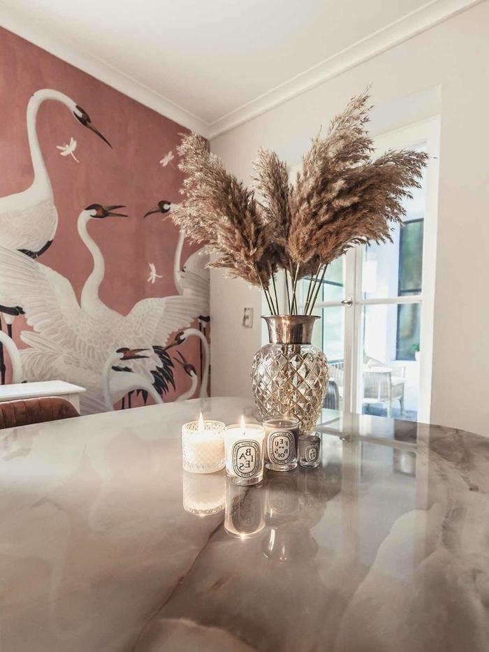 papier peint terracotta motifs cigogne plante plumeau table marbre bougies vase verre déco salle à manger moderne