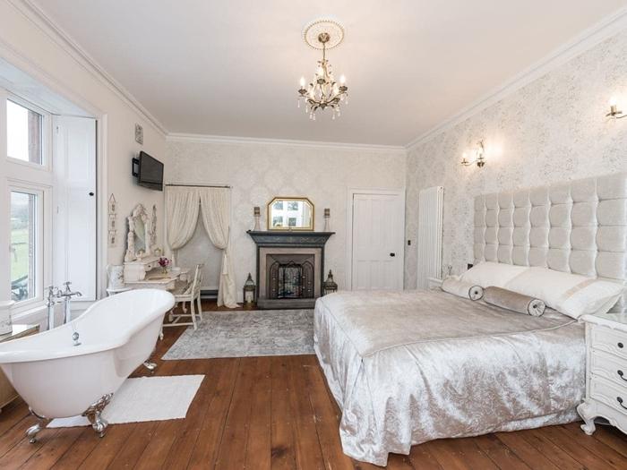 parquet bois salle d eau dans chambre couverture de lit lustre rideaux blancs cheminée décorative miroir or papier peint