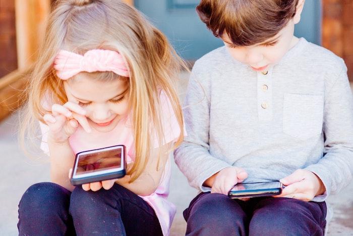 petite fille aux cheveux blonds petit garcon avec portable a la main comment garder vos enfants en securite
