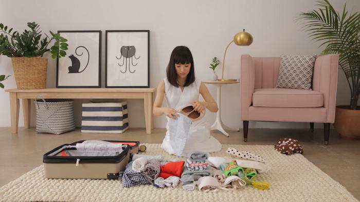 pilage marie kondo comment faire sa valise salle de sejour avec un fauteuil rose et deux tableaux