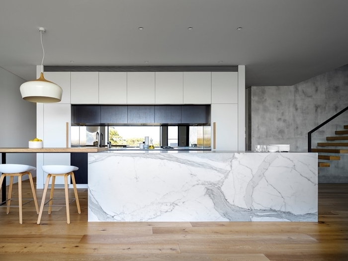 plafond avec éclairage spots led meubles haut noir mat agencement cuisine avec îlot bar marbre et bois plan de travail marbre