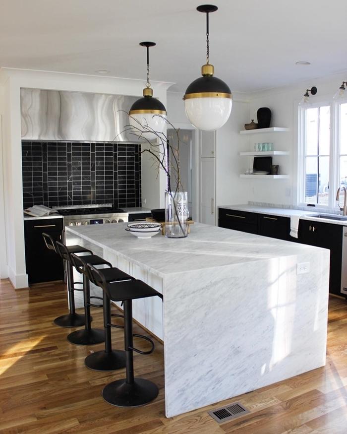 plan de travail marbre blanc chaise de bar noir mat revêtement de sol cuisine parquet bois lampe suspendue noir blanc avec accents or
