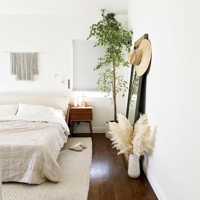 plante chambre à coucher meuble de chevet bois parquet bois foncé tapis blanc macramé suspension fleur de pampa deco